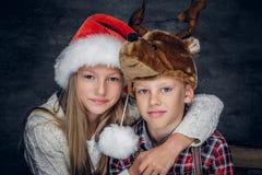 Un muchacho y una muchacha en sombreros de la Navidad Imagen de archivo