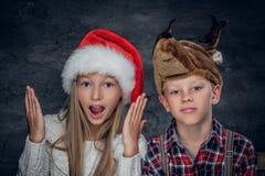 Un muchacho y una muchacha en sombreros de la Navidad Fotografía de archivo