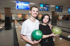 Un muchacho y una muchacha hermosos con las bolas en sus manos presentan en la cámara mientras que juega en el club que rueda Foto de archivo libre de regalías