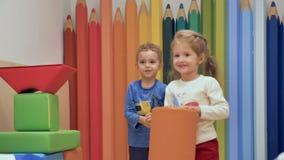 Un muchacho y una muchacha juegan en una esquina de los niños almacen de metraje de vídeo