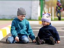 Un muchacho y una muchacha que se sientan en el asfalto Fotografía de archivo libre de regalías