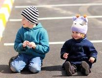 Un muchacho y una muchacha que se sientan en el asfalto Foto de archivo libre de regalías