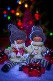 Un muchacho y una muchacha que se sientan en la nieve con las estrellas en el fondo de luces festivas Imagen de archivo libre de regalías