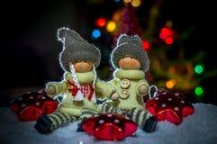 Un muchacho y una muchacha que se sientan en la nieve con las estrellas en el fondo de luces festivas Imagenes de archivo