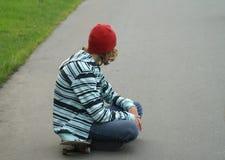 Un muchacho y una tarjeta del patín Imagen de archivo libre de regalías
