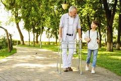 Un muchacho y un viejo hombre en los zancos para los adultos están caminando en el parque Fotos de archivo