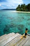 Un muelle del barco y una playa tropical Foto de archivo libre de regalías