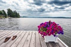 Un muelle en el lago con sandalias Foto de archivo
