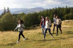 Un multi gruppo etnico di cinque giovani amici adulti sorride mentre cammina su un percorso rurale durante l'aumento della montag fotografia stock