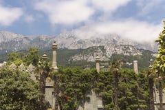 Un mur avec les tourelles mauresques, envahies avec la verdure luxuriante et une vue des crêtes d'AI-Pétri dans les nuages image stock