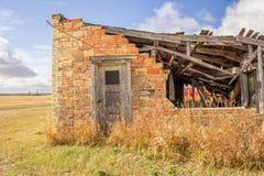 Un mur de briques partiel avec une porte grise Photo stock