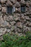 Un mur en pierre avec des barres Photographie stock libre de droits