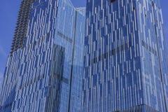Un mur rideau en verre sur la surface externe d'un bâtiment urbain moderne image stock