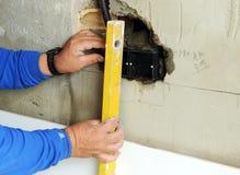 Un muratore che controlla allineamento con il livello Fotografia Stock