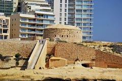 Un muro di mattoni con le scale del mattone che conducono giù sopra alla spiaggia a Malta fotografia stock libera da diritti
