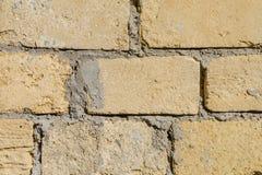 Un muro di mattoni della pietra gialla immagini stock