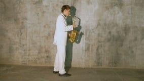 Un musicien dans un costume blanc joue le saxophone clips vidéos