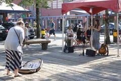 Un musicien de rue exécute aux astuces d'île de Granville et d'un touriste tandis qu'elle exécute L'île de Granville à Vancouver  photographie stock libre de droits