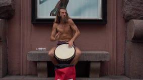 Un musicien de rue joue le tambour Hippies charismatiques au centre de la ville Le batteur joue des motifs africains banque de vidéos