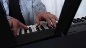Un musicien joue le synthétiseur Plan rapproché des mains et des clés banque de vidéos