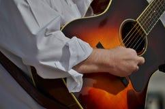 Un musicista che strumming una chitarra. Fotografia Stock