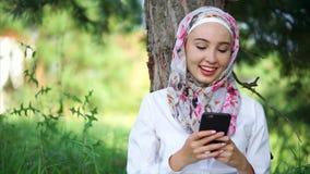 Un musulmán en hijab comunica en el teléfono con los amigos, ella se sienta en un parque almacen de video