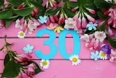 Un número brillante 30 y flores Imágenes de archivo libres de regalías