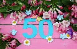 Un número brillante 50 y flores Fotos de archivo libres de regalías