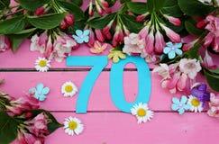 Un número brillante 70 y flores Imágenes de archivo libres de regalías