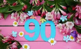 Un número brillante 90 y flores Imagen de archivo