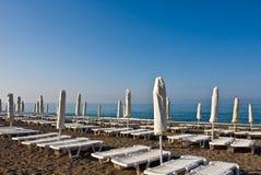 Un número de camas y de paraguas del tablón en una playa Fotografía de archivo