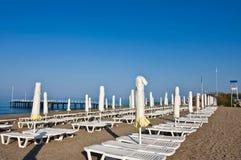 Un número de camas y de paraguas del tablón en una playa imagen de archivo