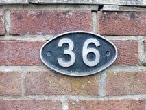 Un número de matrícula en una pared de ladrillo con 36 en ella Fotos de archivo libres de regalías