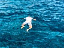 Un nadador de sexo masculino en una camiseta blanca, los pantalones cortos y la máscara, gafas del buceo con escafandra con un tu foto de archivo libre de regalías