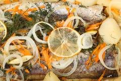 Un nasello marinato con le patate e le spezie al forno nel primo piano del forno Fotografie Stock Libere da Diritti
