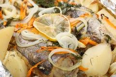Un nasello marinato con le patate e le spezie in una ciotola di vetro al forno nel forno Fotografie Stock Libere da Diritti
