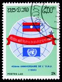UN and national Flag, United Nations, 40th Anniversary serie, circa 1985. MOSCOW, RUSSIA - FEBRUARY 9, 2019: A stamp printed in Laos shows UN and national Flag royalty free stock image