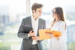 Un negocio diverso del hombre y de la mujer combina en su edificio de oficinas de la compañía que camina en pasillo y disscuss so foto de archivo