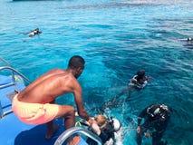 Un negro, buceadores de ayuda del hombre atlético atlético moreno, árabe en trajes negros del buceo con escafandra con las botell foto de archivo libre de regalías