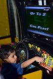 Un neonato che gioca elettronicamente game& controllato x27; s nella stazione del gioco fotografie stock