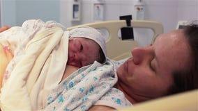 Un neonato si trova sul seno di una madre felice nell'ospedale I primi minuti di vita stock footage