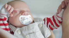 Un neonato sonnolento con una tettarella che tiene una mano femminile stock footage
