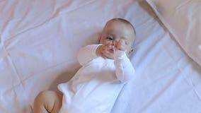 Un neonato sveglio sta trovandosi sul letto nella camera da letto Ritratto video d archivio