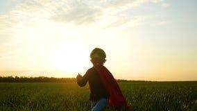 Un niño alegre en un traje del super héroe corre a través de la hierba verde a la cámara en un fondo de la puesta del sol almacen de video
