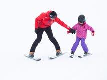 Un niño aprende esquiar con un coche en las montañas Fotos de archivo