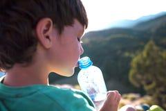 Un niño bebe el agua de una botella Fotos de archivo