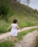 Un niño camina descalzo en el camino arenoso imagen de archivo libre de regalías