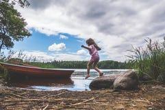 Un niño camina en el agua, lago, río, cerca del barco en el w fotos de archivo