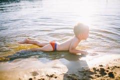 Un niño caucásico de tres años en troncos de natación rojos miente en su estómago en el agua cerca de la orilla del río de una pl Fotos de archivo