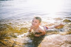 Un niño caucásico de tres años en troncos de natación rojos miente en su estómago en el agua cerca de la orilla del río de una pl Imagen de archivo